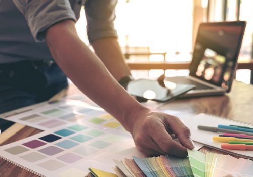 Color samples, color swatch samples, Draw architecture, Graphic designer selecting on colour chart, pens at workplace, Working with laptop and tablet on wooden desk.